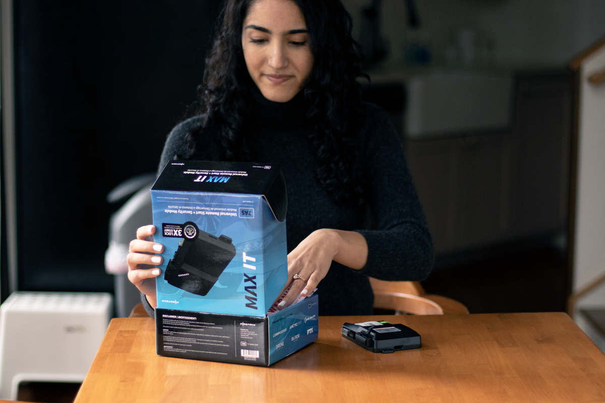 woman holding compustar max it remote start and security kit